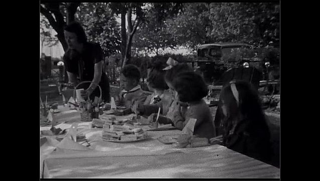 1930s: UNITED STATES: ladies smile at camera. Boy looks at camera. Children at table in garden for party.