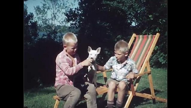 1940s: UNITED STATES: view of sea from garden. Boys with cat and dog. Boys with black kitten in garden. Boys in deckchair