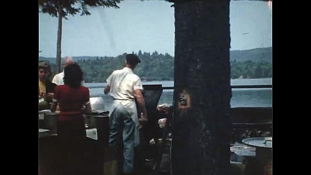 1940s: UNITED STATES: view of lake through trees. People on boat. Man on bicycle. Ladies serve food in woods.