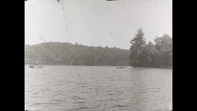 1940s: UNITED STATES: lady on boat on lake. View across lake. Man emerges from trees, Lady in woods