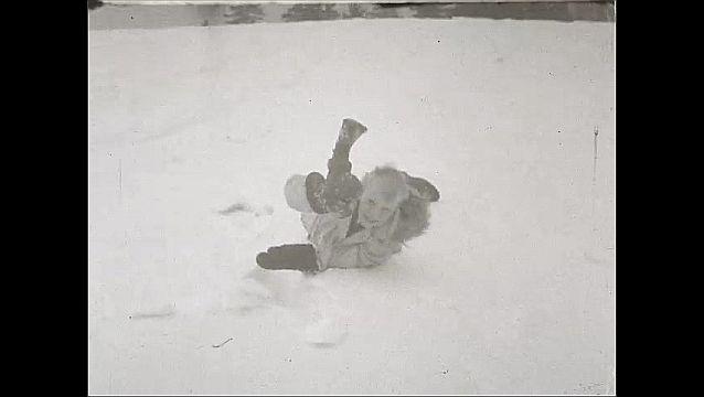1940s: UNITED STATES: children in snow. Boy lies in snow. Boy runs in snow. Man in snow.