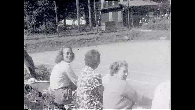 1940s: Young man in glasses and suit speaks on lake's edge. Women and men sit next to tennis court, look and smile at camera. Little girl holds up hands to cheek and cheeses for camera.