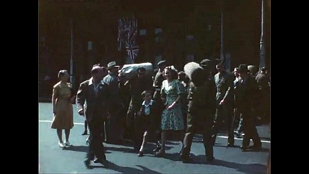 1940s: Bridge. Lady stands in car door and speaks to two boys on side of road. WWII soldiers arrive home, walk through streets with duffel bags, flanked by family, people wait in crowds on street.