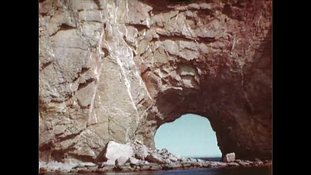 1940s: Quebec. Enormous rock formation in middle of ocean. Teen boy on deck of boat heading towards rock, younger boy waves. Natural arch in giant rock, neighboring rock formation.