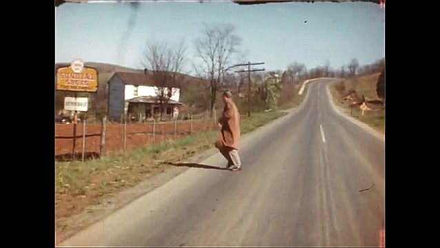 1940s: Blonde boy stoops by bush, smiles. Cars parked behind building. Teen boy in glasses runs in road, comes forward holding white hat, talking. Overlooking valley, smoke from factory.