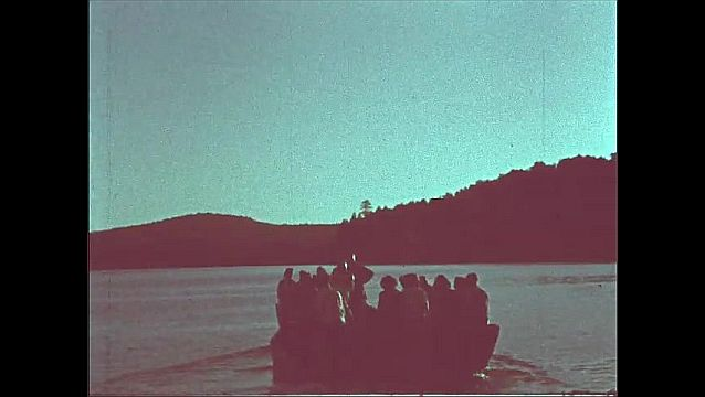 1940s: People sit on boat on shore of lake, mountains behind. Boat pushes off from shore with over a dozen men and women. Boat slowly floats on lake, make in center with hands on hips.