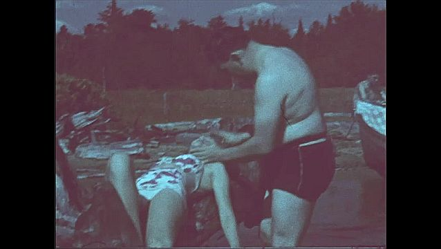 1940s: Woman in swimsuit reclines on driftwood tree in lake, arm dangling in water. Burly shirtless man massages her face, man watches by end of boat.