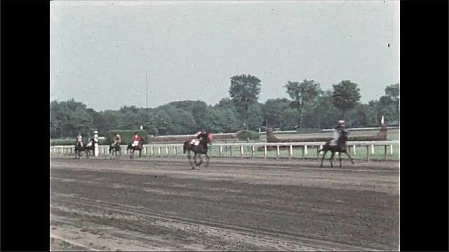 1940s: People in stands of horse racing track. Jockeys ride horses along race track.