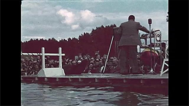 1940s: Man directs Sea Lion to jump over bar in pool, before an audience. Sea Lion jumps over bar again.