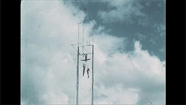 1940s: Three acrobats are suspended above ground high up on trapeze tower, doing tricks.