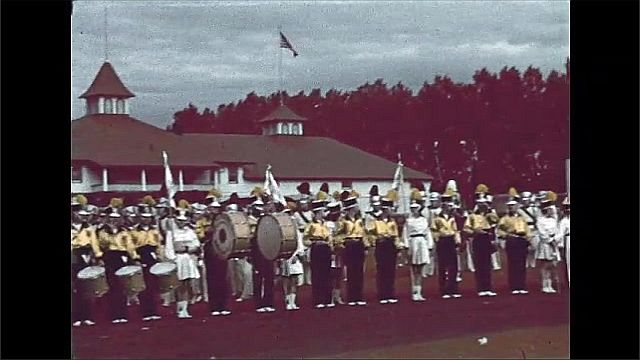 1940s: Marching band gathers and prepares for performance on side of field. Marching band begins warming up.