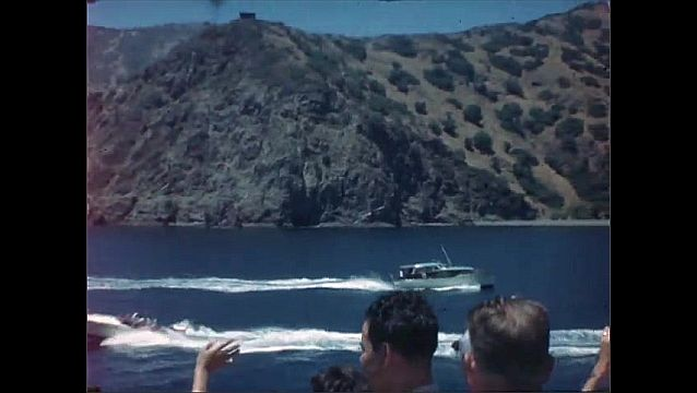 1940s: Boat trip, sunshine, scrubby Mediterranean cliffs, hills, coastline. Group of people on deck wave at passing boats.