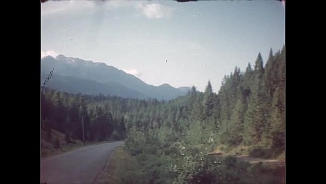 """1940s: Mountains, river, trees. """"To Banff."""" Road, dense evergreen forest. Hotel Windermere, vines trained up porch."""
