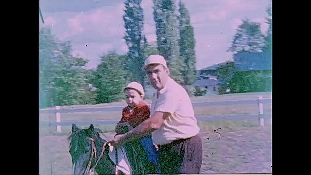 1940s: Man walks next to child on horse, guides horse.