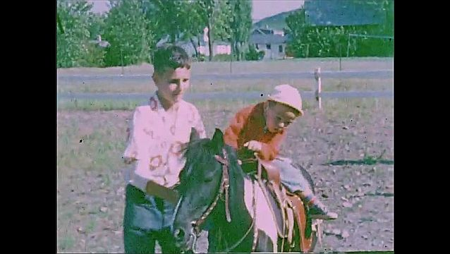 1940s: Child rides on horse. Boy guides horse and child around ring.