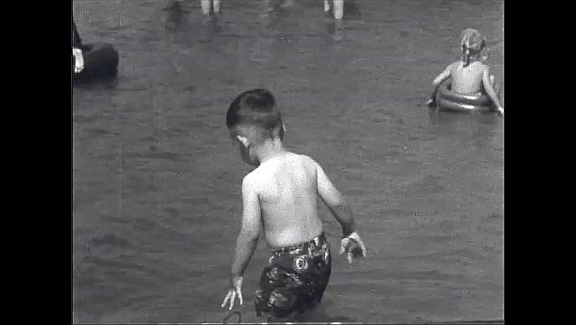 1930s: UNITED STATES: families play in lake. Slide in lake. Boy plays by beach. Sand by beach