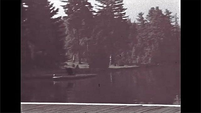 1940s: UNITED STATES: man walks down steps from house. Ladies walk across garden. Plane on water by jetty. Boys fishing from jetty. Lady looks in lake