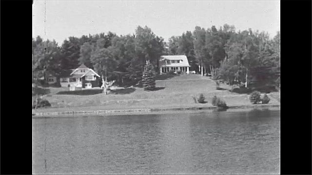 1940s: UNITED STATES: view across lake to house and shore. House and gardens. Trees by lake.