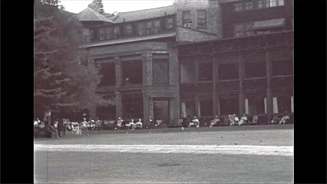 1940s: UNITED STATES: Lake Placid Club building and gardens. People on lawn. Tree in park.