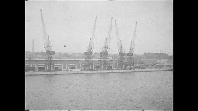 1930s: View of piers, city skyline. Cranes by pier.
