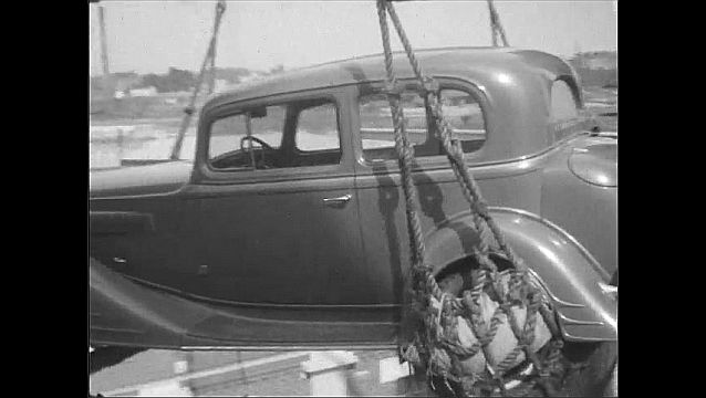 1930s: High angle, men on boat attaching ropes to car. Car lifting from boat. People walking up and down steps to ship.