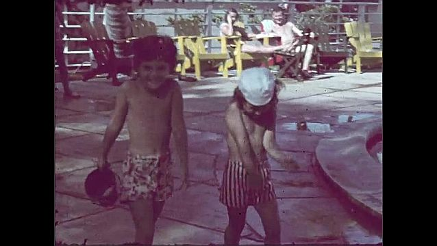 1940s: Women in yard with kids. Girls walking by pool. Long shot, men on diving boards, pan across pool.