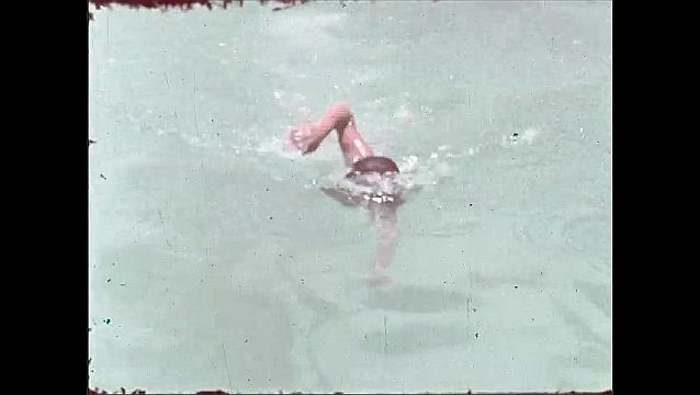 1940s: Long shot, man walking by pool. Man dives into pool, swims toward camera, talks by side of pool.