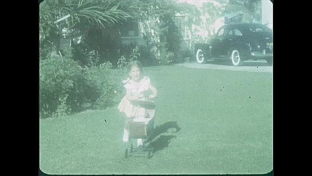 1940s: Girl in yard, walks toward camera, blows kisses. Close up shots of girl. Girl by playhouse. Girl pushes toy stroller. Girl with stroller. Girl runs toward house. Girl runs toward camera.
