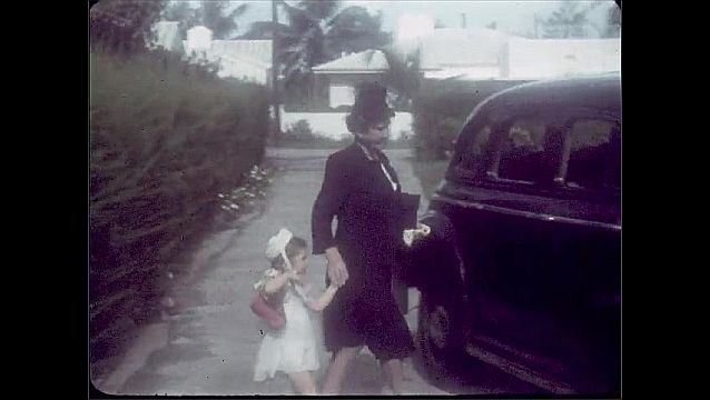 1940s: Girl standing by car. Woman enters, adjusts girl's dress. Woman and girl by car. Woman opens car door for girl. Girl waves from car window.