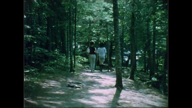 1950s: Women walk down path through forest.