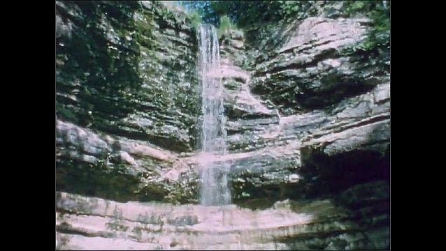 1950s: Woman walks along lodge under waterfall.
