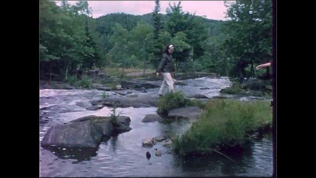 1950s: Women walk along rocks in river.