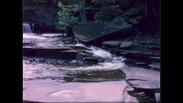 1950s: Woman stands on rock by small waterfalls in river. Woman walks across rocks.