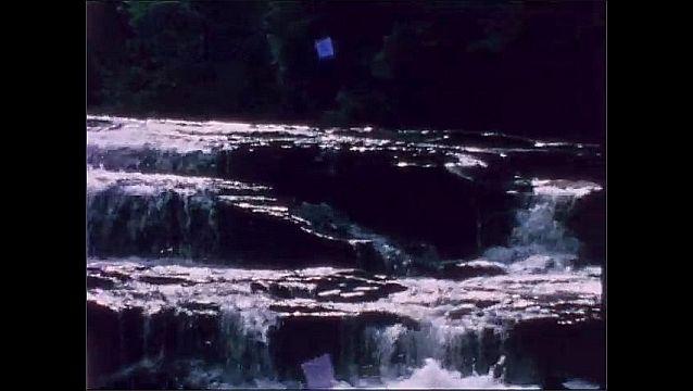 1950s: Women stand on rock next to waterfall. Man walks across rocks by waterfall.