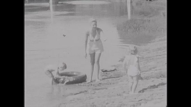 1940s: Little girl plays on beach. Woman and children play on beach, in water.