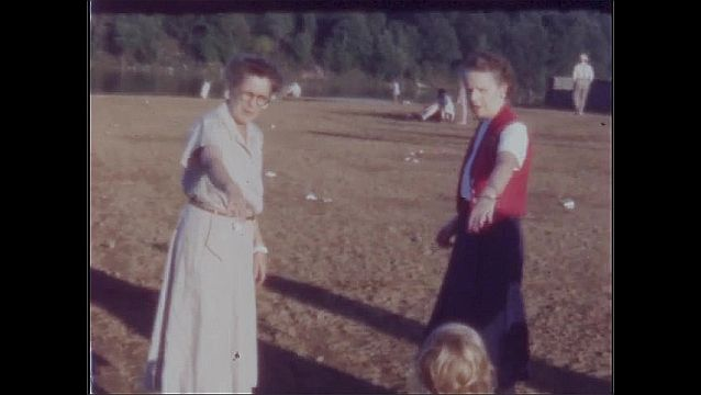 1940s: Women stand on grass next to lake. People play catch. Women hold their hands out to young girl.