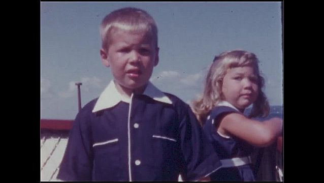 1940s: UNITED STATES: girl and boy on boat. Girl smiles at brother.