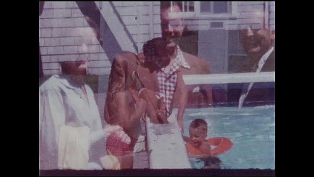 1940s: UNITED STATES: people outside building. Children play in pool. Lady by pool