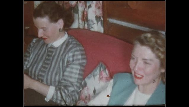 1940s: UNITED STATES: lady and man sit and drink. Ladies sit on sofa. Lady smokes cigarette