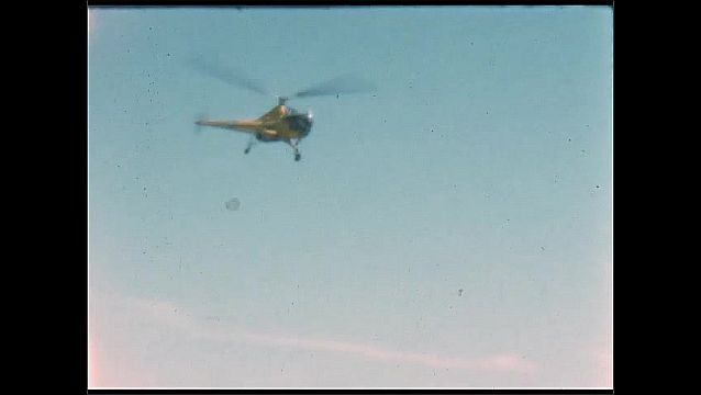 1940s: UNITED STATES: helicopter above ground. Helicopter comes in to land on runway. View of runway.