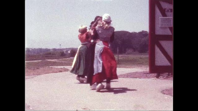 1970s: UNITED STATES: girls dance in clogs by windmill.