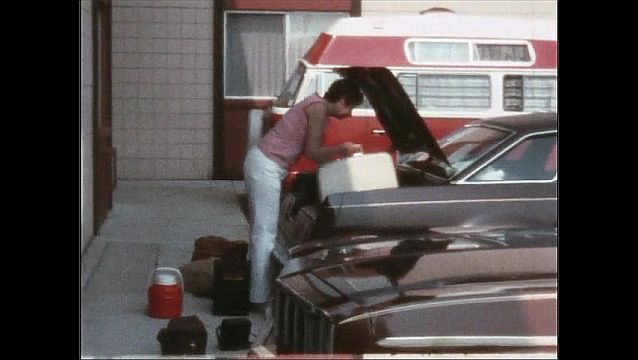 1970s: UNITED STATES: lady packs cases in car.