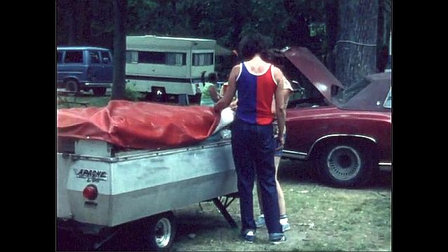 1970s: UNITED STATES: ladies put cover over trailer tent. Trailer on back of car.