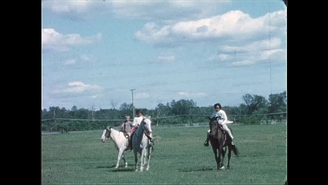 1940s: UNITED STATES: riders on horses in field. Girl on horse.