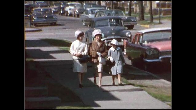 1940s: Neighborhood.  Traffic.  Women and girl walk down street.