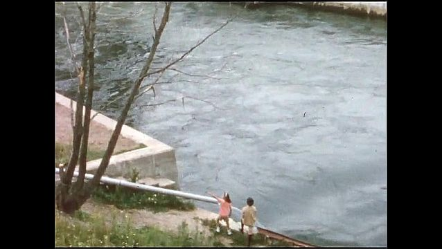 1940s: Water passes through dam.  Woman and girl stand near reservoir.