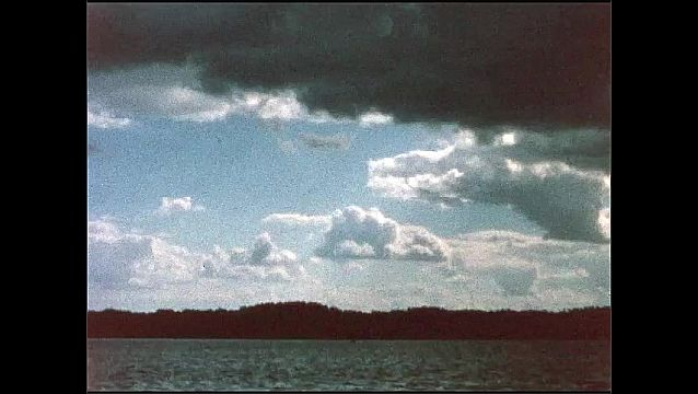 1940s: Water.  Trees.  Clouds.  Women ride on boat.