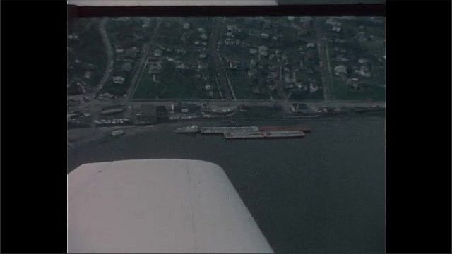 1940s: UNITED STATES: small plane on tarmac. Open door on cockpit. Plane flies over flooded area. Flood damage from above. Flight over bridge
