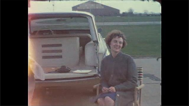1940s: UNITED STATES: children in car. Plane on runway. Man smokes cigar by car. Lady sits in deckchair at airport. Lady pokes tongue out at camera