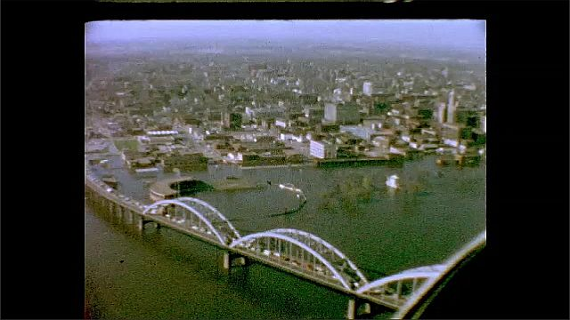 1940s: UNITED STATES: trees in flood water. Bridge over water. Overhead view of flood